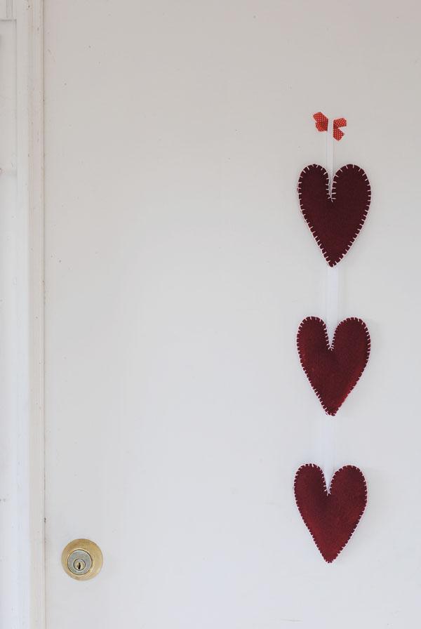 Penduricalho com corações de feltro pendurado atrás da porta