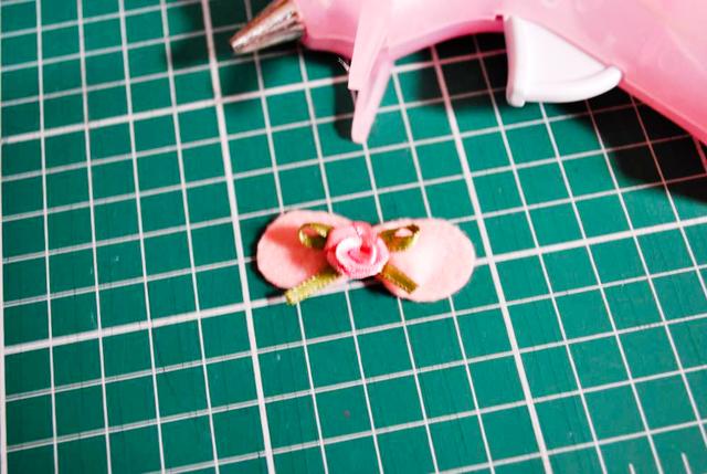 Cole uma florzinha de rococó no centro do lacinho de feltro com cola quente