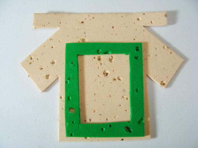 1) Corte no E.V.A. a camisa (de acordo com o molde ou se preferir desenhe à  mão livre); corte também uma pequena moldura. Cole a moldura sobre a camisa.