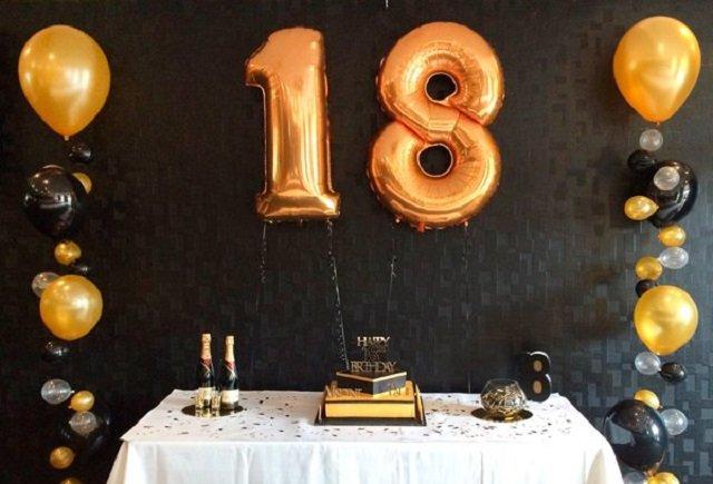 Decoração de festa com balões dourado, preto e prata