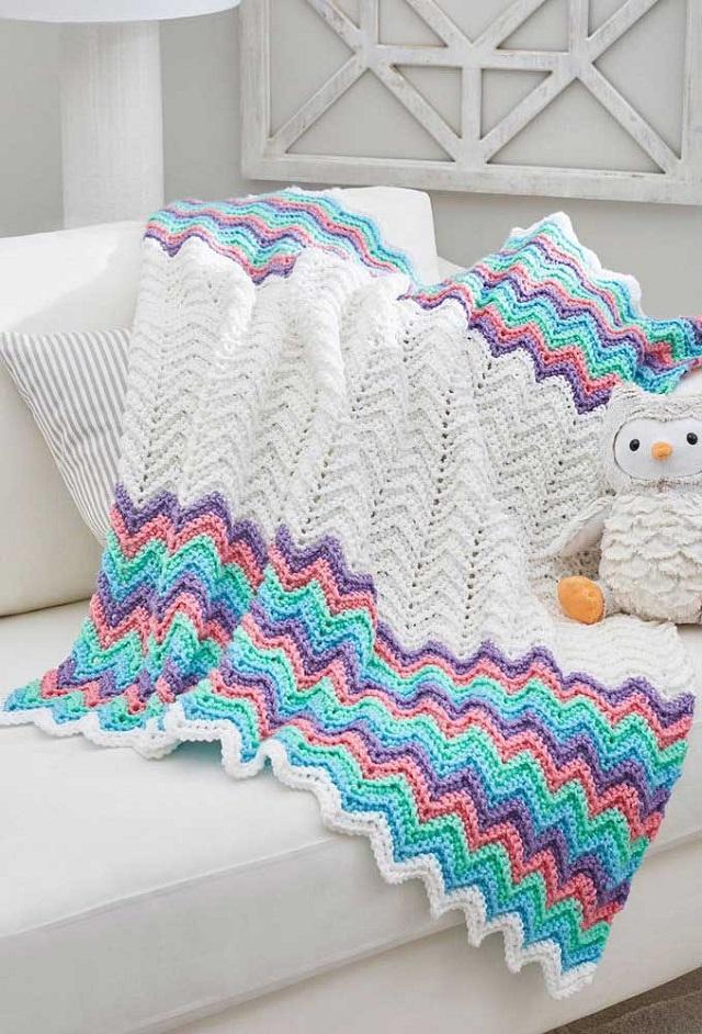 Manta de crochê tunisiano branca e com listas coloridas